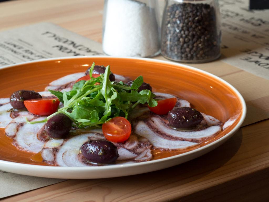 Karpátsio – carpaccio z marynowanej ośmiornicy polane oryginalną grecką oliwą, oliwki kalamata, pita z rozmarynem
