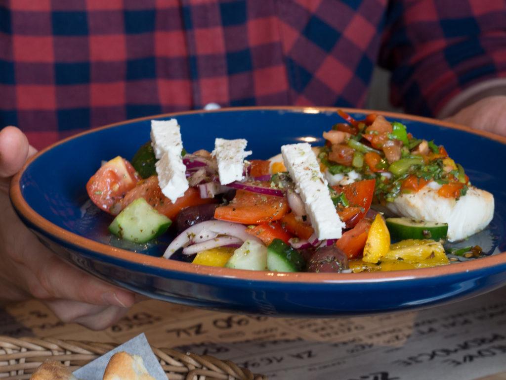 Psari me horiatiki – pieczony filet z dorsza podany z salsą paprykowo-pomidorową ze świeżą kolendrą, sałatka grecka z serem feta i oliwkami kalamata