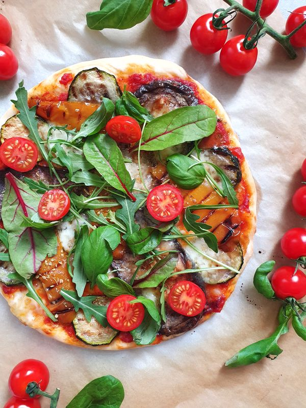 pizza pełnoziarnista z grillowanymi warzywami, rukolą i pomidorkami